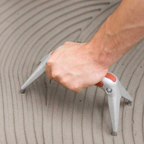 LTHGS Raimondi Fido Ergonomic Support spreading thin set mortar with notched trowel on floor