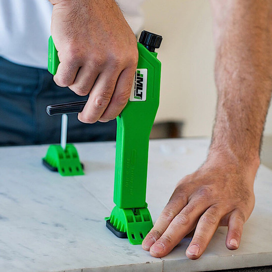 tile or stone, lower the tension locking cap over the re-usable connecting tab to tile or stone surface then, slide cap in direction of the grout joint to engage the lock