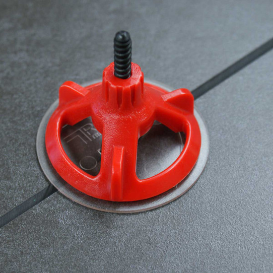 free-spinning leveling cap spins down the spacer screw, to secure the cap and level the tile with only one hand