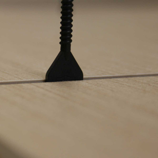 One tile adhesive has cured, use a rubbet mallet to remove the cap and threaded post from the installed tile